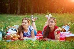 Twee mooie meisjesrust op een picknick in het bos stock afbeeldingen