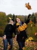 Twee mooie meisjesvrienden met de herfst doorbladert Stock Afbeeldingen
