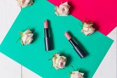 Twee mooie roze lippenstift turkooise en roze, witte gekleurde achtergrond met bloemen van rozen, luchtmening, close-up, schoonhe stock fotografie