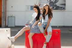 Twee mooie slanke meisjes met lang haar, die toevallige uitrusting dragen, zitten op de omheining op de weg en de glimlach stock afbeelding