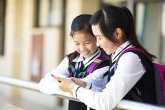 Twee mooie studentenmeisjes die de slimme telefoon kijken royalty-vrije stock foto's