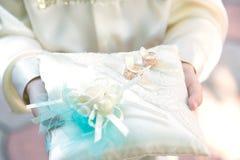 Twee mooie trouwringen op kussen in de handen van een kind Stock Afbeeldingen