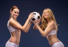 Twee mooie voetbalventilators in greep de voetbalbal Royalty-vrije Stock Afbeeldingen