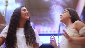 Twee mooie vrolijke meisjes dalen op de roltrap tijdens het winkelen in het winkelcentrum met een goede stemming HD sluit stock videobeelden