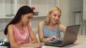 Twee mooie vrouwelijke studenten die samen gebruikend laptop bestuderen stock videobeelden