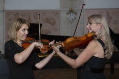 Twee mooie vrouwelijke violisten die viool spelen stock afbeelding