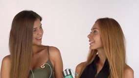 Twee mooie vrouwelijke vrienden die aan de camera glimlachen, die in trainingkleding stellen stock footage