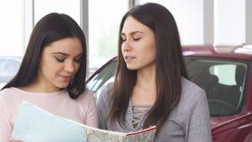 Twee mooie vrouwelijke vrienden die bestemming op een kaart zoeken stock video