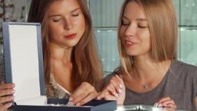 Twee mooie vrouwelijke vrienden die juwelen onderzoeken plaatsen in een doos voor verkoop bij de opslag stock videobeelden