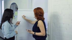 Twee mooie vrouwen bereiden presentatie op kantoor voor stock footage