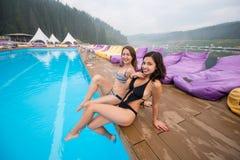 Twee mooie vrouwen bij de rand van toevlucht zwembad terwijl het genieten van van vakantie stock afbeeldingen