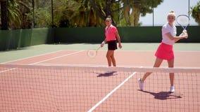 Twee mooie vrouwen die een spel van tennisdubbelen spelen stock video