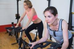 Twee mooie vrouwen die oefeningen op fietsen doen bij gymnastiek Stock Afbeelding