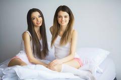 Twee mooie vrouwen die op een bed zitten en bekijken camera Royalty-vrije Stock Afbeeldingen