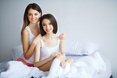 Twee mooie vrouwen die op een bed zitten en bekijken camera Royalty-vrije Stock Foto