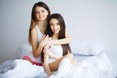 Twee mooie vrouwen die op een bed zitten en bekijken camera Stock Afbeelding