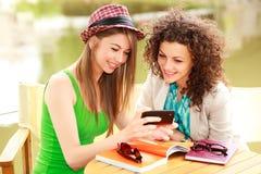 Twee mooie vrouwen die op een slim-telefoon spelen royalty-vrije stock afbeeldingen