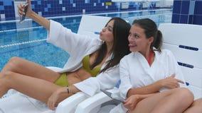 Twee mooie vrouwen die selfies het liggen op chaise-longues nemen dichtbij het zwembad stock videobeelden