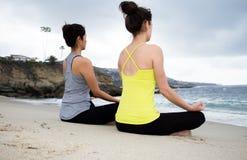 Twee mooie vrouwen die yoga uitoefenen bij strand Royalty-vrije Stock Afbeeldingen