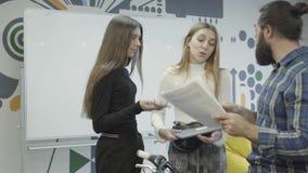 Twee mooie vrouwen die zich communiceren in het bureau verenigen De gebaarde mens op zijn fiets komt aan hen en geeft documenten stock videobeelden