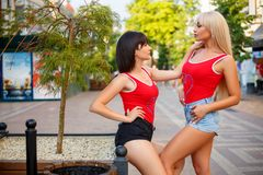 Twee mooie vrouwen die zich op de straat in borrels bevinden stock foto's