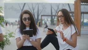 Twee mooie vrouwen lezen in openlucht boeken stock videobeelden