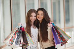 Twee mooie Vrouwen met het winkelen zakken naast een supermarkt Royalty-vrije Stock Foto