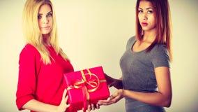 Twee mooie vrouwen met rode giftdoos stock foto