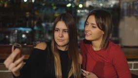 Twee mooie vrouwen nemen een selfie bij de bar stock video