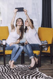 Twee mooie vrouwenvrienden die gelukkige glimlachen thuis spreken Royalty-vrije Stock Afbeeldingen