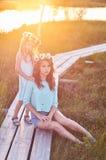 Twee mooie zusters die zich tegen de achtergrond van een mooi landschap, gang op het gebied dichtbij een vijver bij zonsondergang Royalty-vrije Stock Fotografie