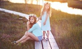 Twee mooie zusters die zich tegen de achtergrond van een mooi landschap, gang op het gebied dichtbij een vijver bij zonsondergang Royalty-vrije Stock Foto