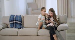 Twee mooie zusters terwijl het zitten op de bank die een spel op smartphone in een ruime moderne woonkamer spelen, zeer stock videobeelden