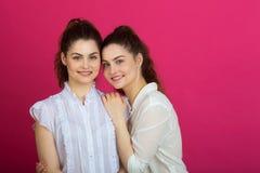 Twee mooie zusters tweelingmeisjes in witte blouses stock afbeelding