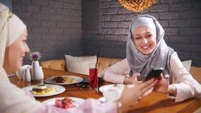 Twee moslimvrouwen die bij een lijst in een restaurant zitten en en in hun telefoons zitten Het tonen van beelden in de telefoon stock video