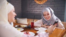 Twee moslimvrouwen die bij een lijst in een restaurant zitten en en in hun telefoons zitten Het tonen van de beelden stock footage