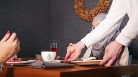Twee moslimvrouwen die bij een lijst in een restaurant zitten Een kelner brengt de orde stock videobeelden