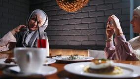 Twee moslimvrouwen die bij een lijst in een restaurant zitten Een vrouw die een foto van haar vriend nemen stock video