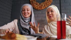 Twee moslimvrouwen die in een restaurant zitten en aan hun vriend spreken stock video