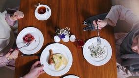 Twee moslimvrouwen die in een restaurant zitten die salade eten Een kelner brengt een andere schotel stock footage