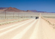 Twee motoren die snel op lange rechte woestijnweg drijven royalty-vrije stock afbeelding