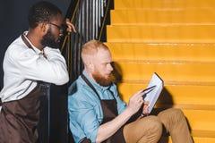 twee multi-etnische eigenaars die van koffiewinkel notitieboekje bekijken en zaken bespreken royalty-vrije stock afbeelding