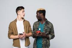 Twee multiraciale vrienden gebruiken hun mobiele die telefoon op witte achtergrond wordt geïsoleerd Telefoonverslaving royalty-vrije stock fotografie