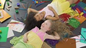 Twee multiraciale vrouwelijke op tapijt liggen en kinderen die, gelukkige kinderjaren lachen stock footage