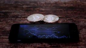 Twee muntstukken bitkoyn, liggend naast smartphone, op het scherm dat een grafiek van citaten, crypto munt toont Royalty-vrije Stock Foto's