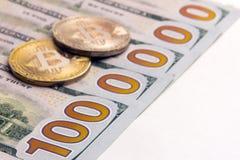 Twee muntstukken van bitcoin op de bankbiljetten van de V.S. De honderd dollarsrekeningen liggen op een witte achtergrond, die ee royalty-vrije stock foto's