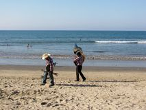 Twee musici wandelen op strand die hun instrumenten dragen stock foto's