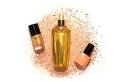 Twee nagellakken en haarolie in gouden fles op beige poeder Royalty-vrije Stock Afbeeldingen