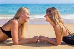 Twee Nederlandse meisjes die tegenovergesteld op strand liggen royalty-vrije stock fotografie