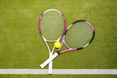 Twee nieuwe roze tennisrackets met een tennisbal op een groen gras Royalty-vrije Stock Fotografie